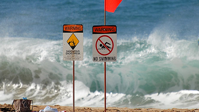 signs warning about dangerous shorebreak