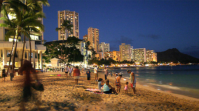 Waikiki beach as the sun goes down and the city light come on