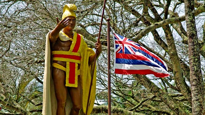 Kamehameha statue next to Hawaiian flag