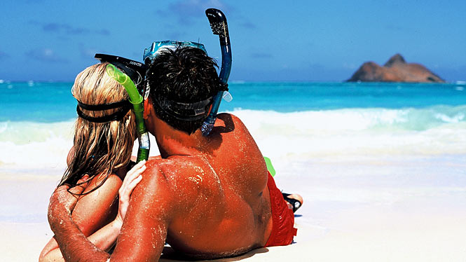 Couple on Oahu, Hawaii beach with snorkel gear on