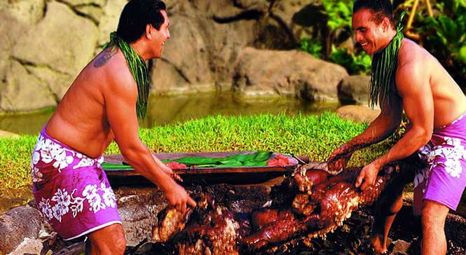 two guys pulling a cooked pig out of ground ready to eat