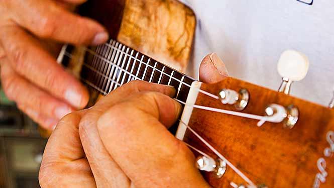 Closeup of Man's fingers playing ukulele