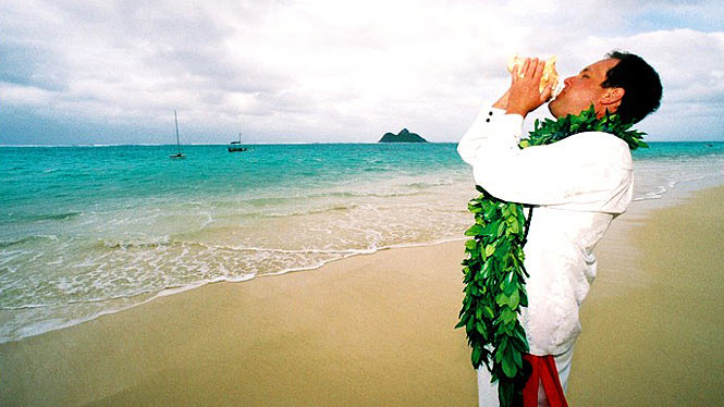 Groom wearing Maile lei and blowing a conch shell