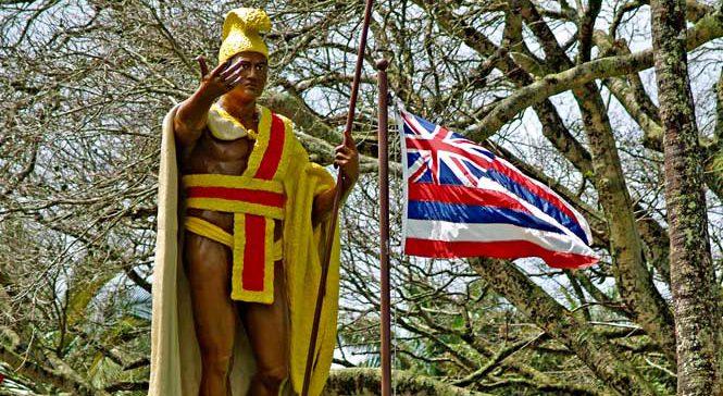 Kamehameha the great statue next to Hawaiian flag