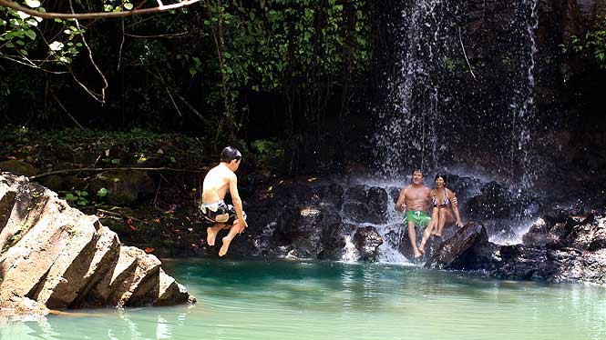 Boy jumping into water, parents sitting under waterfall watching