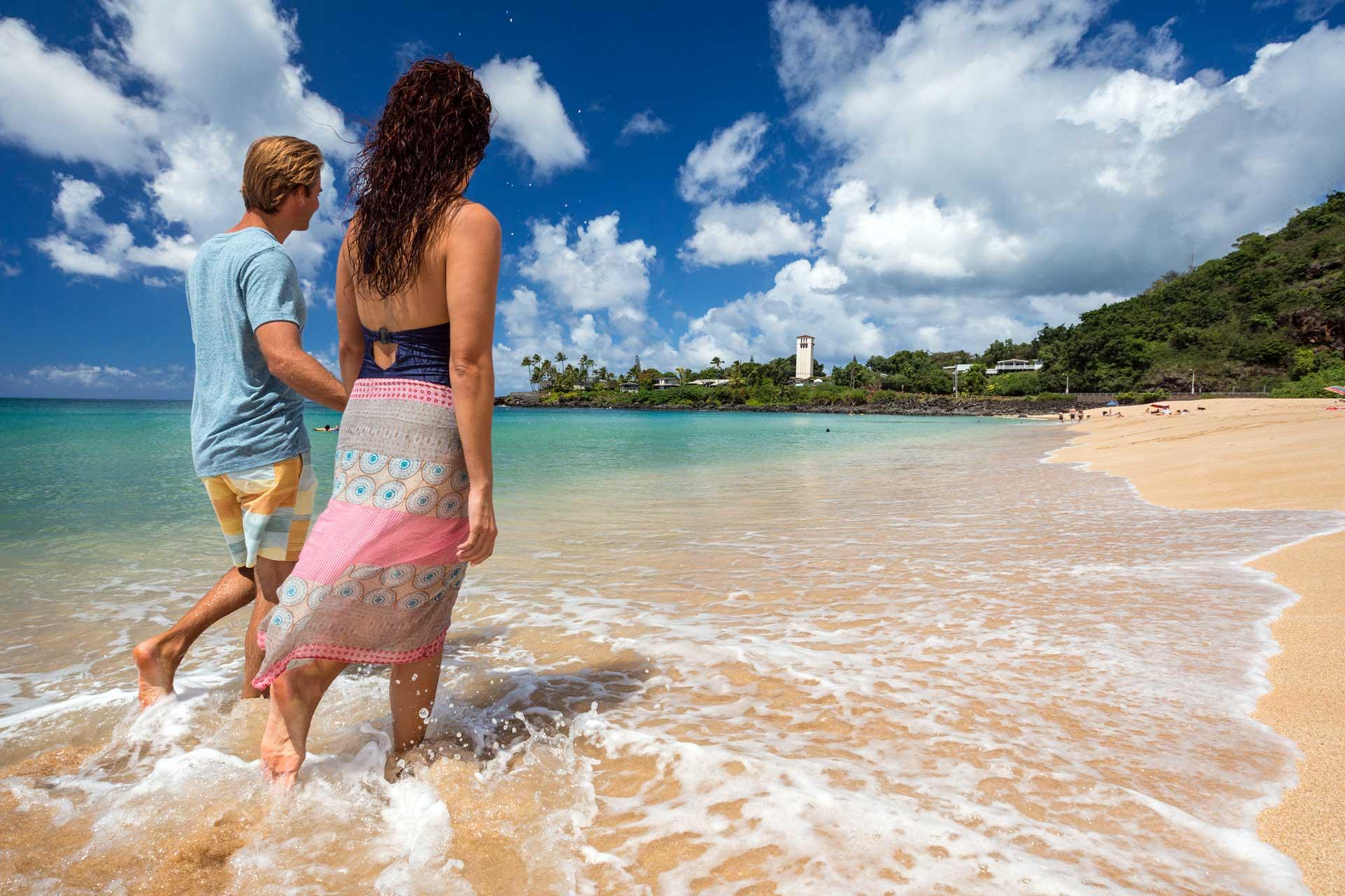 Couple walking on white sand beach of Waimea Bay, Oahu