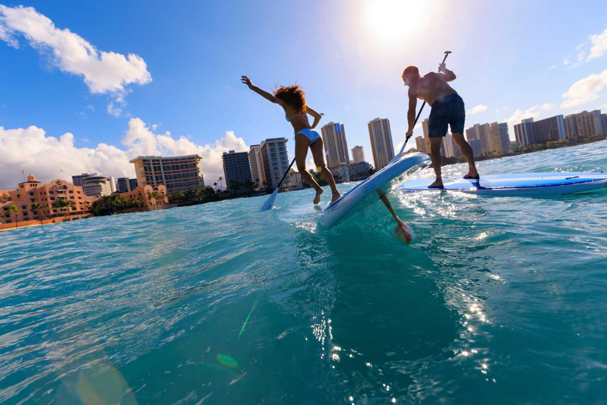 2 paddle boarders playing in the ocean of Waikiki Beach