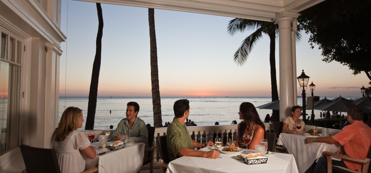 couples sharing dinner at sunset with ocean in background at resturant