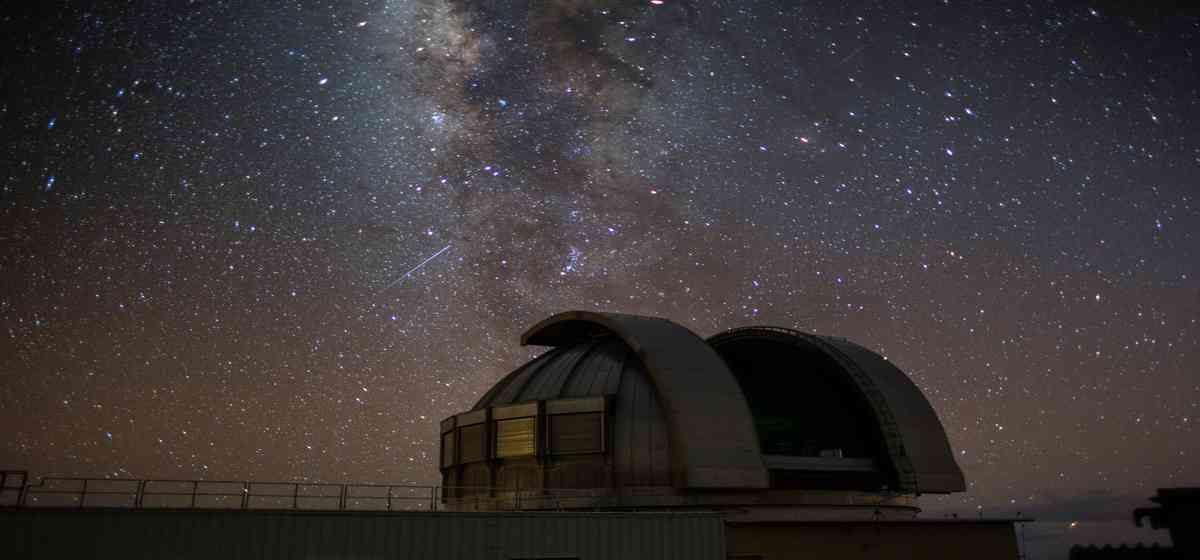 Stars at Mauna Kea with observatory.