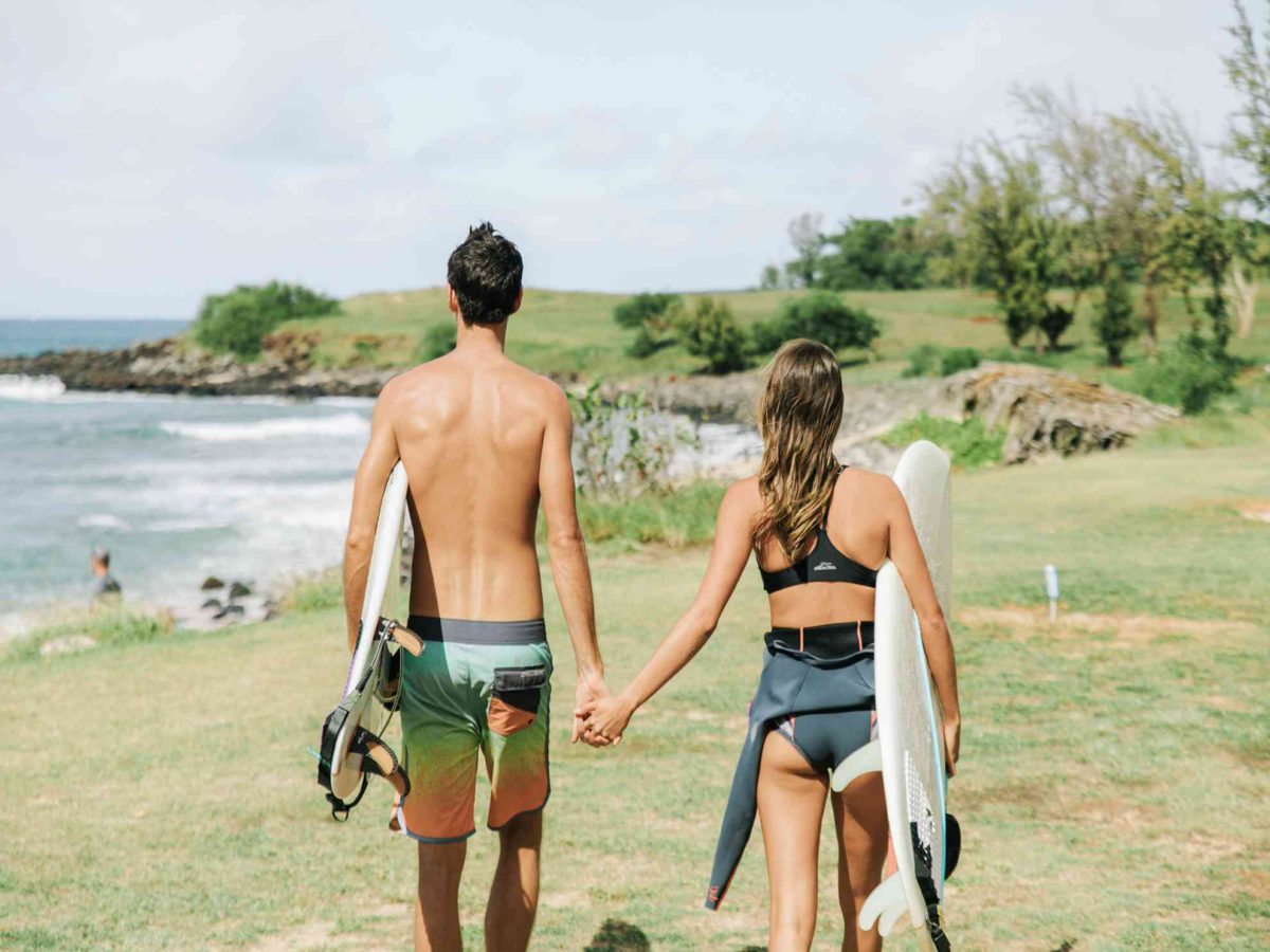 A couple walking on Molokai with two surfboards