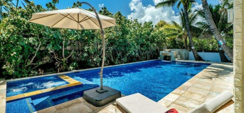 Pool side with jacuzzi and water fall. Palm trees and foliage surrounding the pool.