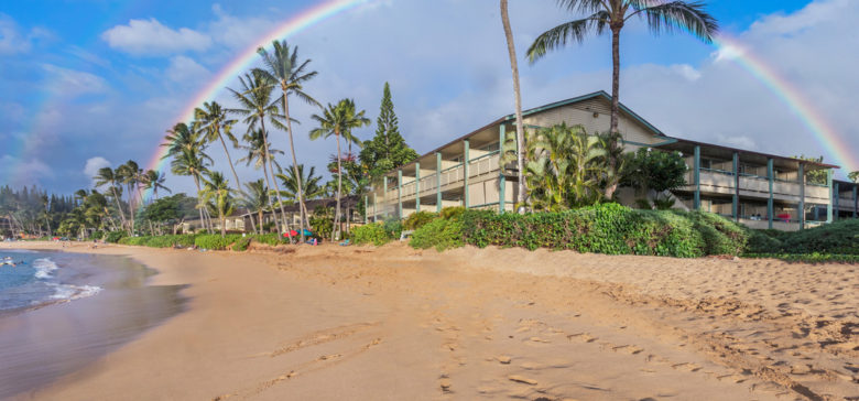 Napili resort from the beach with rainbow over the top of the resort and palm trees.