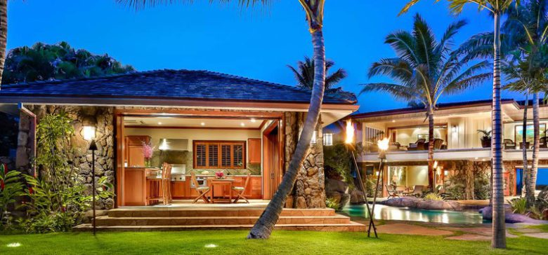 Picture of a beautiful home in Kailua, Hawaii with palm trees and torches.