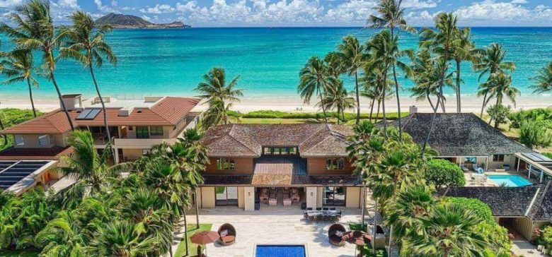 Aerial view of a luxury home in Kailua with pool, home, beach, and palm trees.