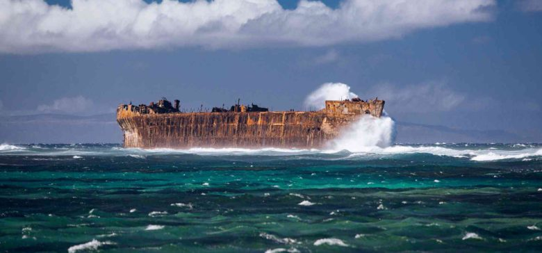 picture of a wrecked cargo ship at shipwreck beach lanai, Hawaii with waves crashing into it.
