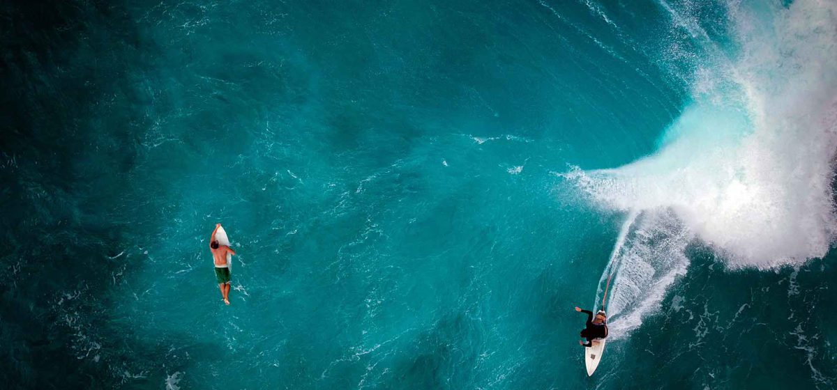 2 people surfing in Hawaii from above