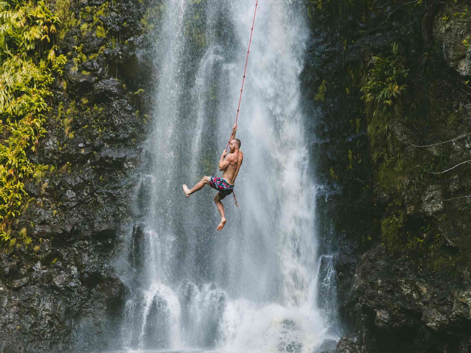 Man hanging onto rope swing at Waimea falls. One of the things to do on the big island.