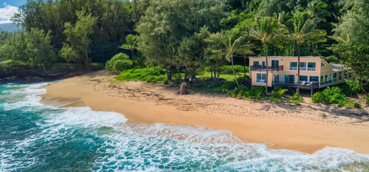 Home right on the white sand beach with waves crashing in an trees surrounding the home.