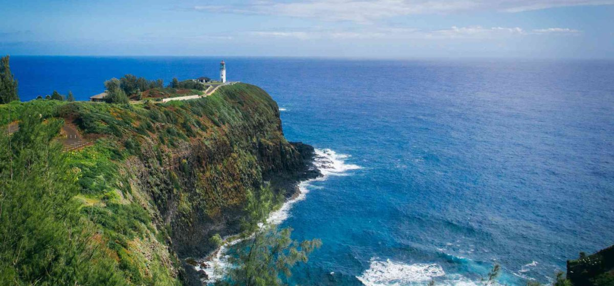 Kilauea Lighthouse as seen from the cliff-side. With the ocean below and clouds in the blue sky.