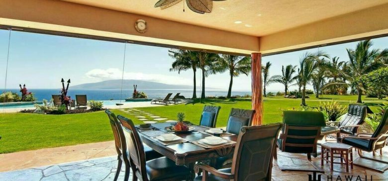 View from Lanai looking out to the ocean with palm trees and outdoor dining area.