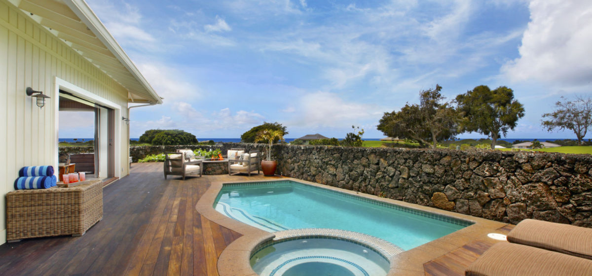 View of the pool and jacuzzi with lava rack wall and ocean in the distant background.