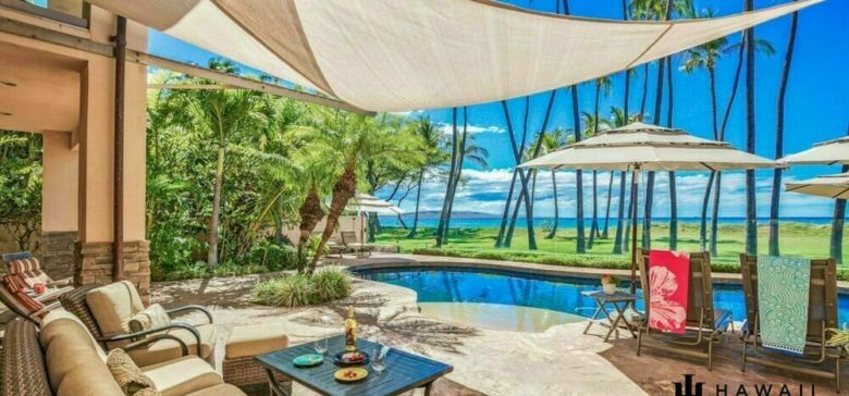 Pool with umbrellas and palm trees. Plenty of beach chairs and a bottle of wine with a small outdoor dining area.