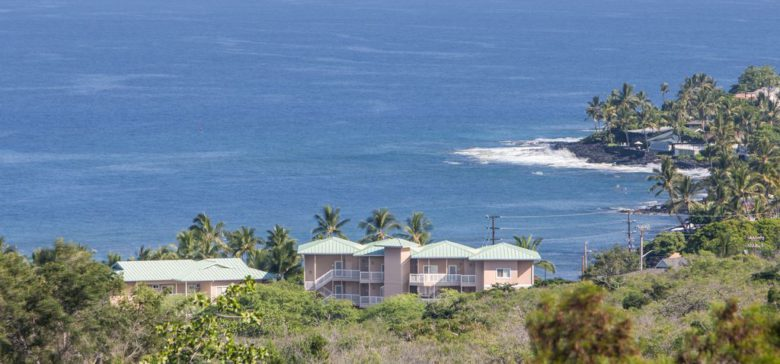 Beach villas at kahaluu with ocean and waves in background surrounded by palm trees.