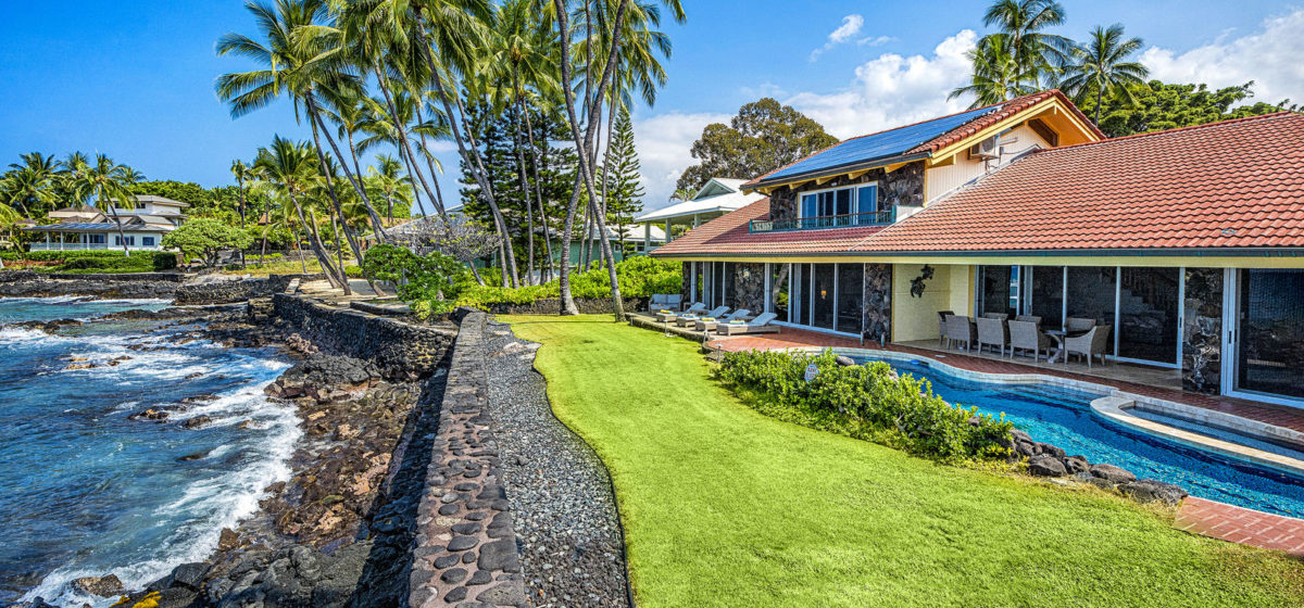Backyard with seawall and green grass. House and pool with beach chairs and palm trees.
