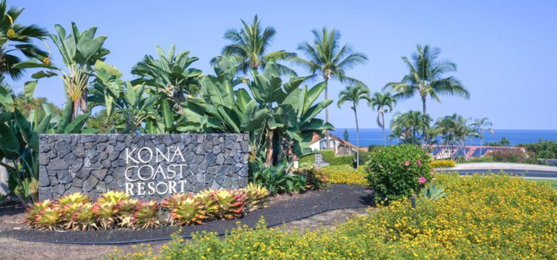 Kona Coast resort sign made out of lava rocks with palm trees and bushes.
