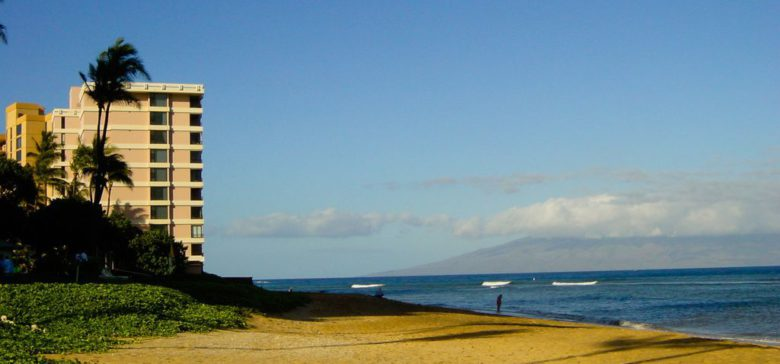 The Maui Kai Beach resort from the beach with the ocean to the right and a man standing in the water.